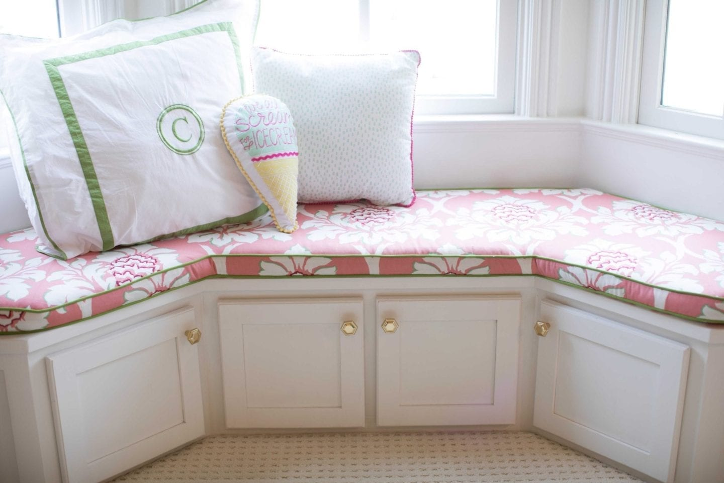 white window seat in a girls bedroom with gold geometrical hardware and madcap cottage fabric covered bench