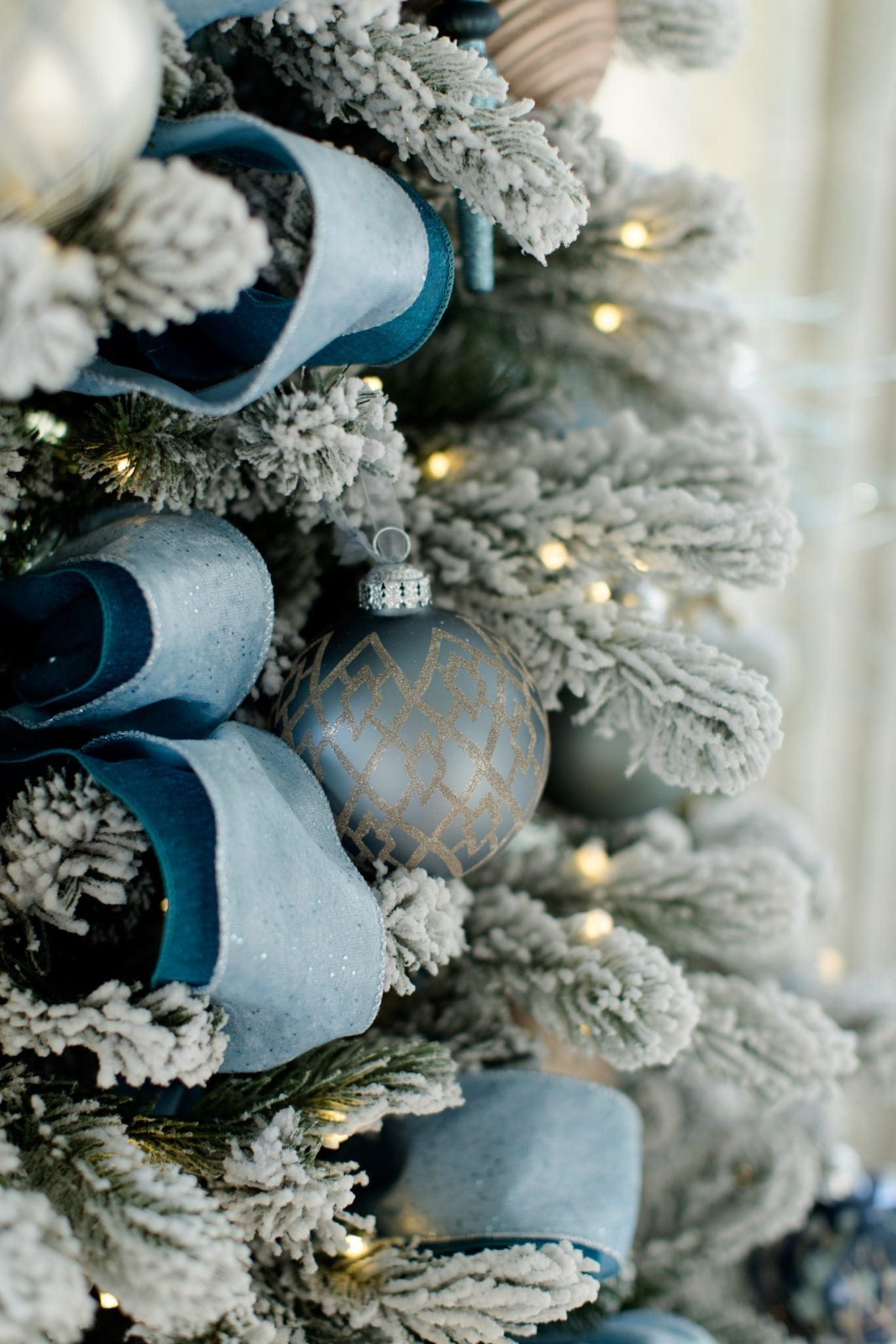 peacock blue and dark blue layered ribbon on pre lit flocked white christmas tree - Peacock Blue Christmas Decorations