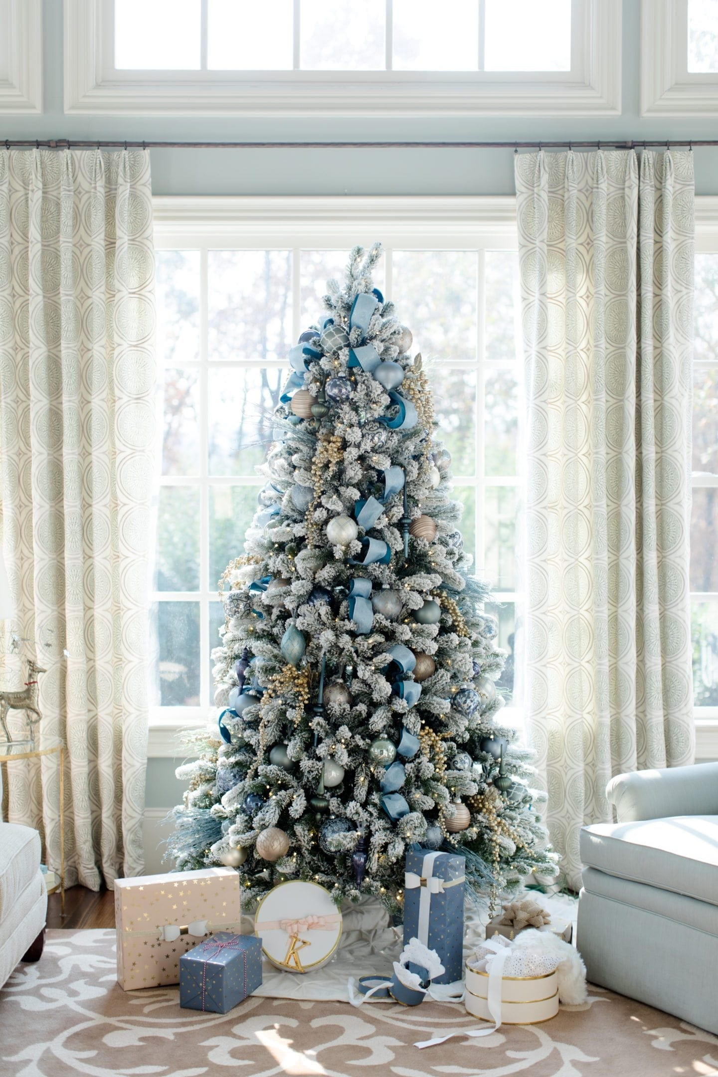 flocked christmas tree with blue glass ornaments and blue ribbon and presents below it