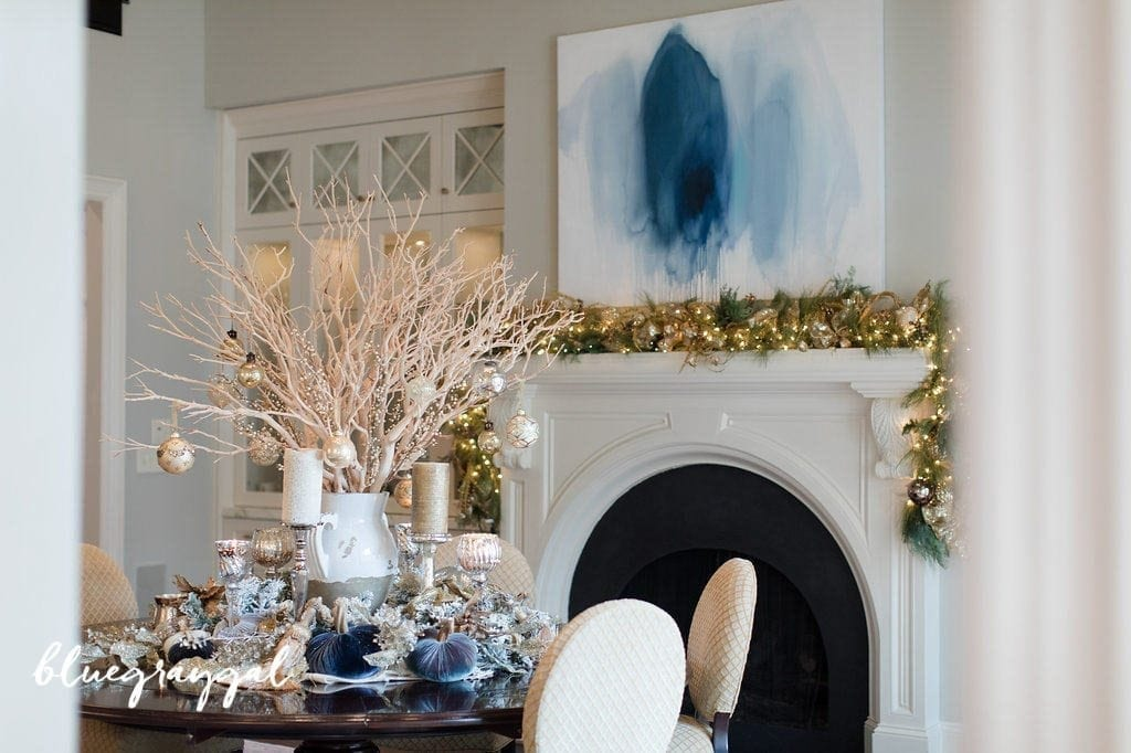 Manzanita branches with christmas ornaments and flocked garland around it in a dining room with blue wall art. How to decorate a table for Thanksgiving. Creating a manzanita centerpiece for a table.