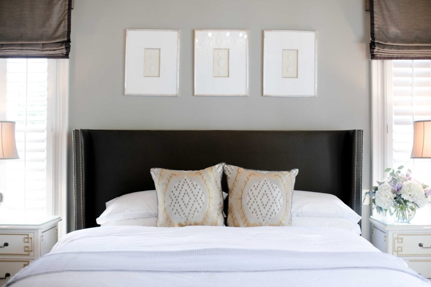How to make a bed using the best white bedding from Bloomingdales linens. Gold and gray throw pillows on Lee Industries headboard. Gray silk bed with Intaglio prints above master bed.