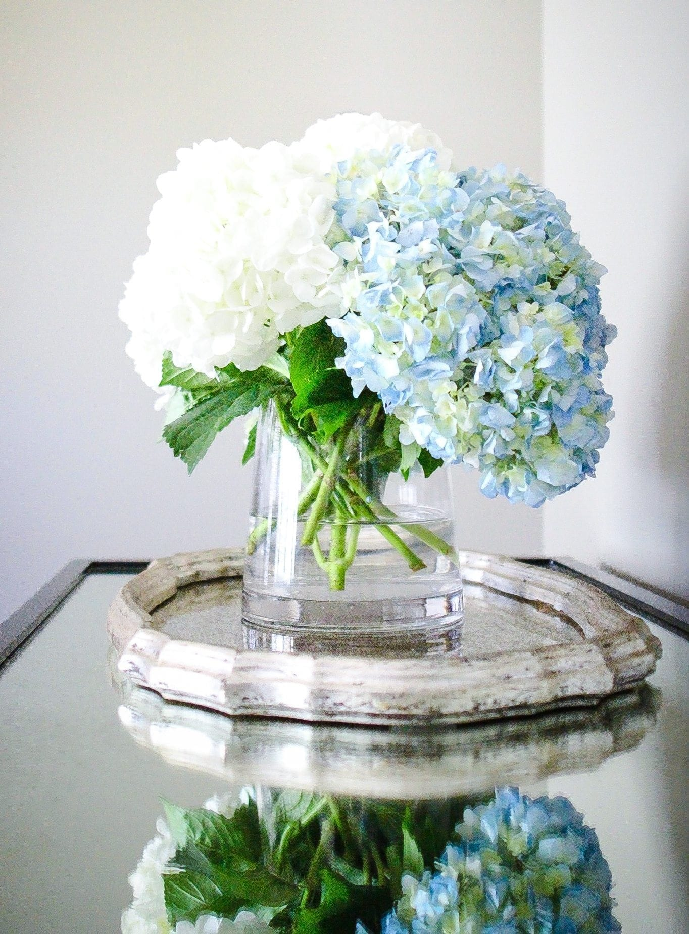 Blue and white hydrangea flower bouquet. Silver mirrored tray on mirrored console table.