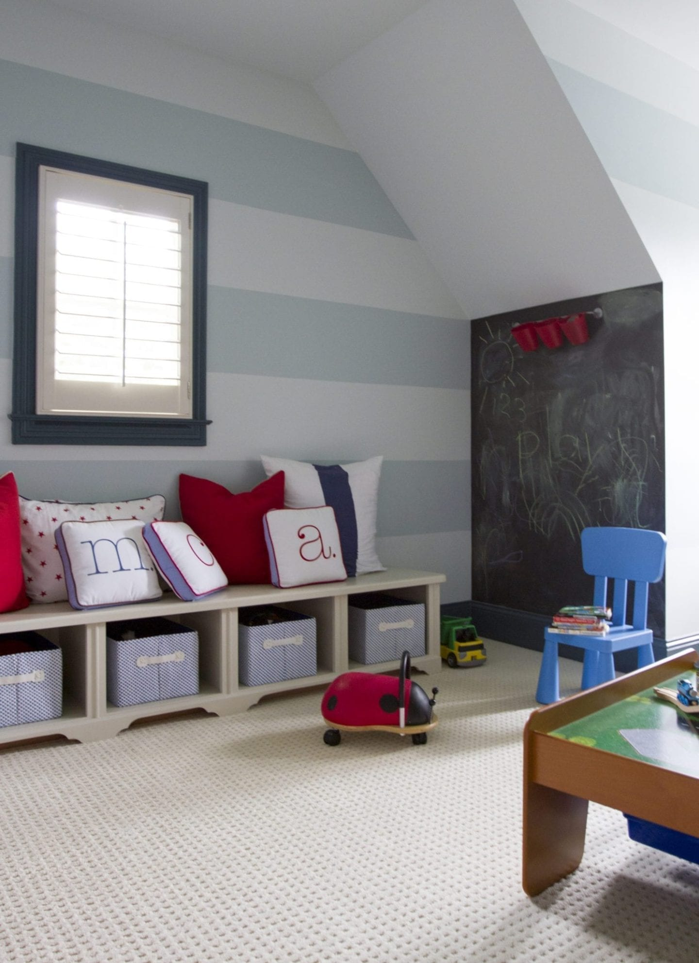 Kids playroom with cabana stripes and chalkboard wall with red blue and white pillows.