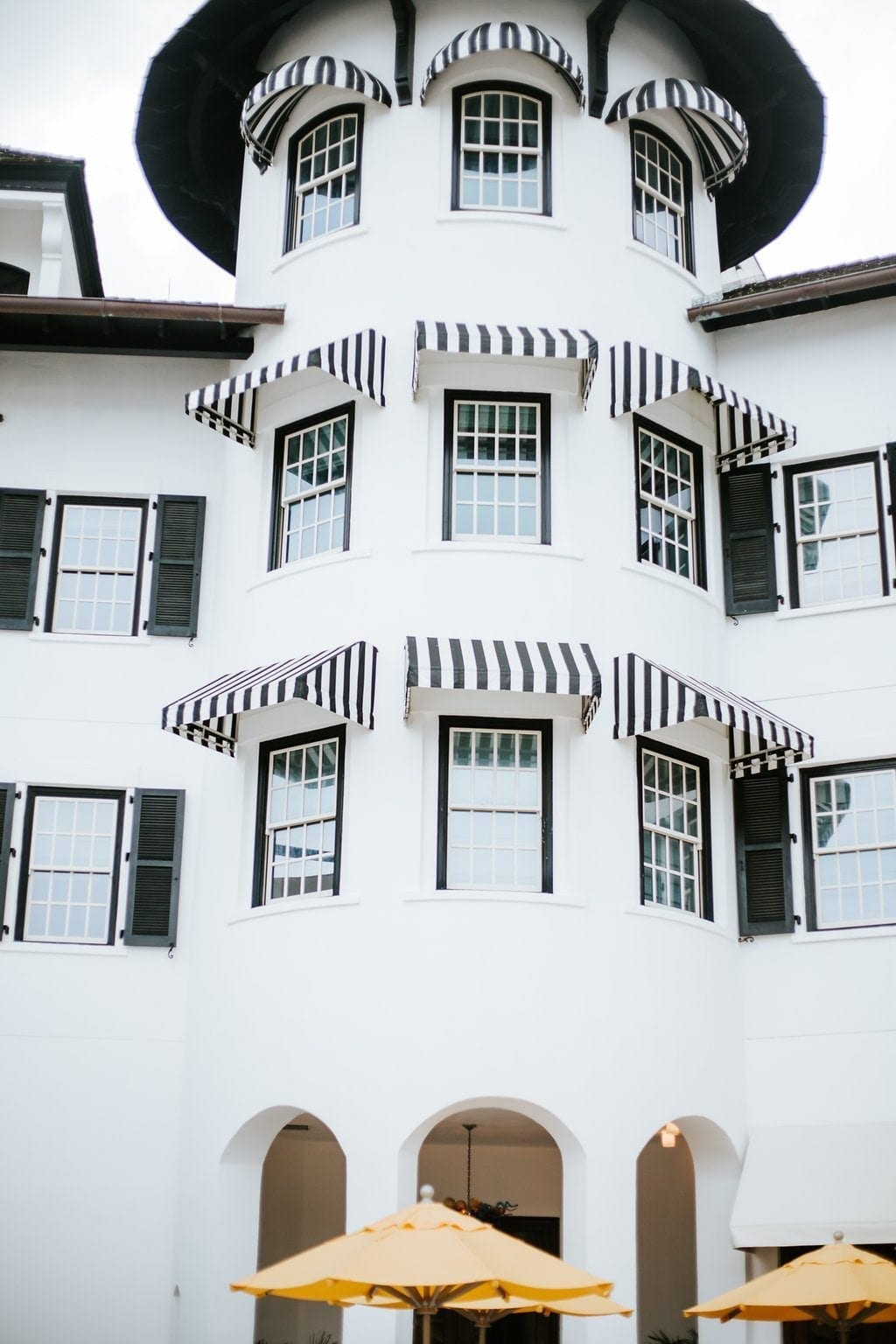 The Pearl hotel in Rosemary Beach is pure eye candy. This boutique hotel is a fantastic place to take family photos in Destin. I love the black and white awning accents with yellow outdoor umbrellas. Outdoor decor and outdoor design at it's finest!