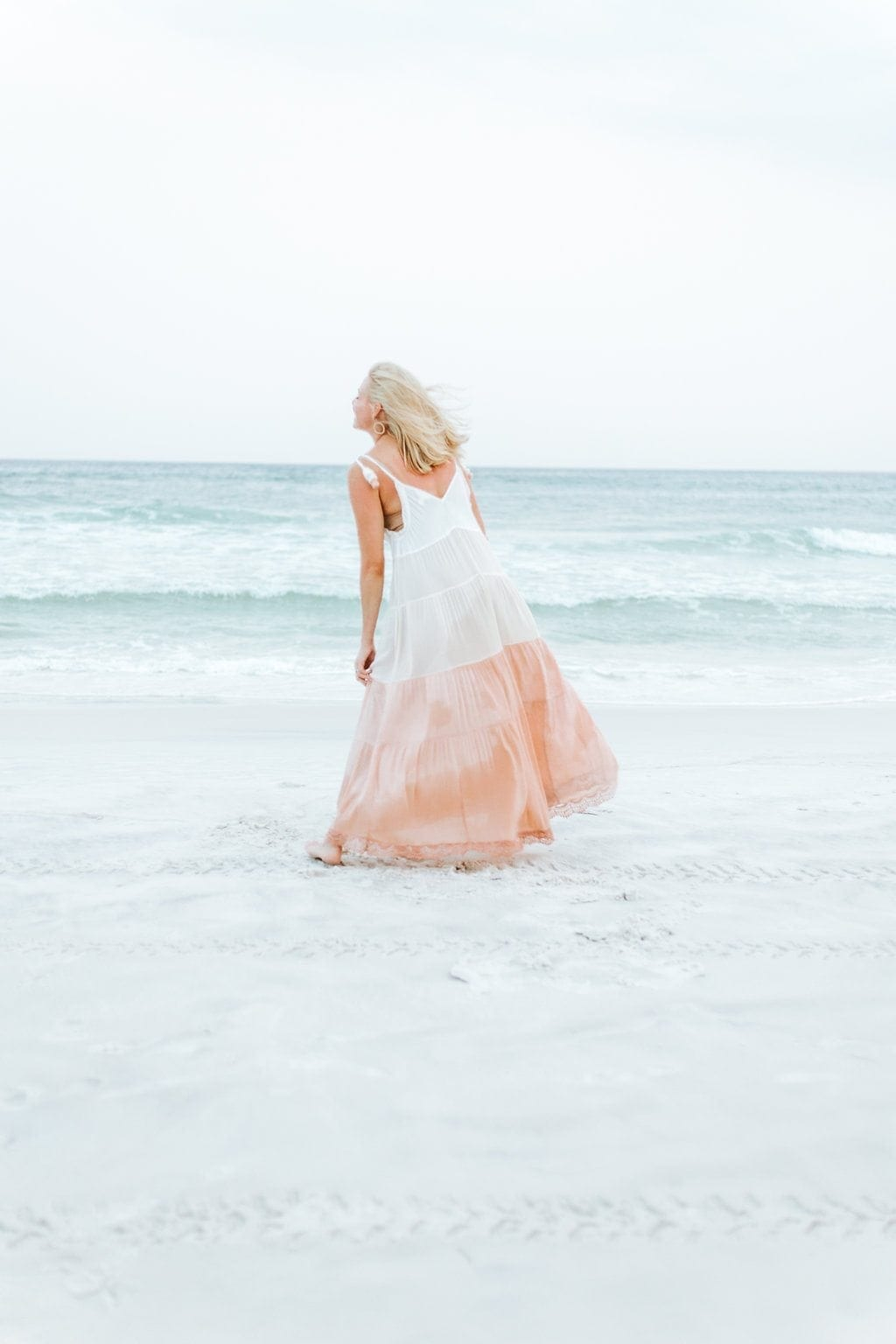 Beach maxi dress. Wind blown hair and a full skirt maxi dress are the perfect mix to wear to the beach on vacation. The soft colors are great to wear for photographs on the beach and then wear to dinner after a day in the sun.