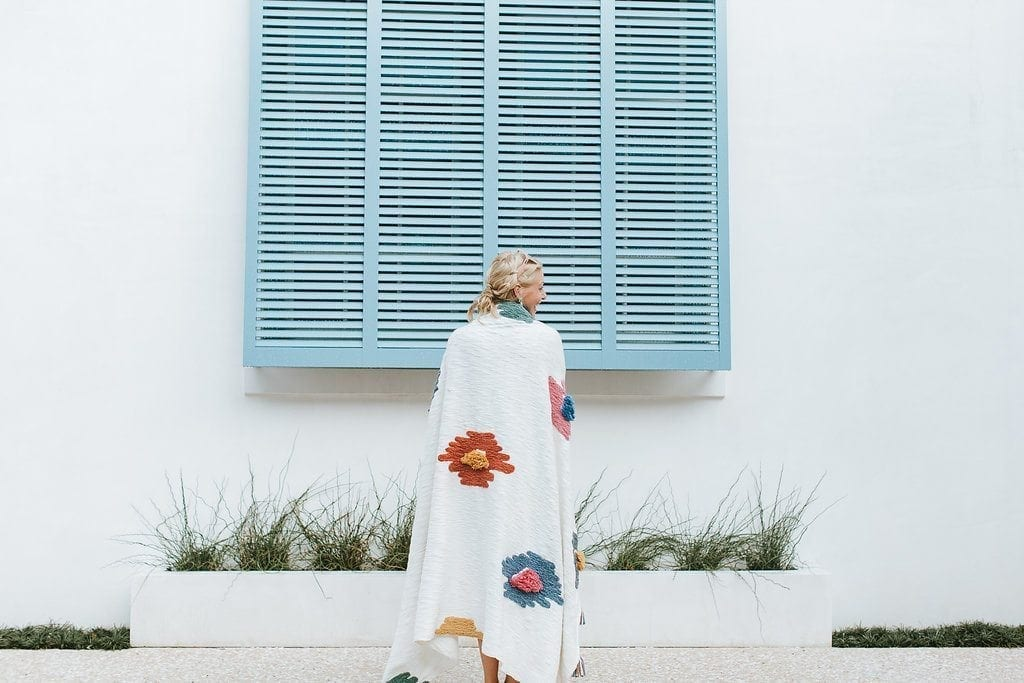 Kelly Page, the home blogger BlueGrayGal, stands in front of a blue and white home in Alys Beach wearing one of the brightly colored Anthropologie throw rugs available.