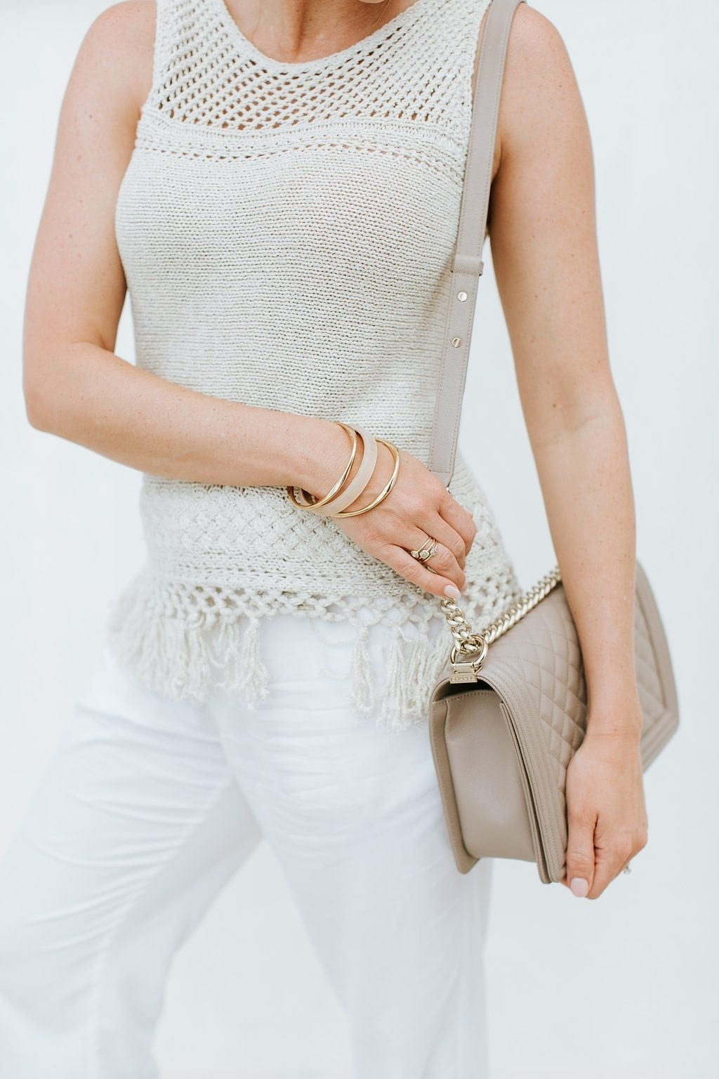 Gold fringe sweater with neutral Chanel Boy bag and gold and nude bangle bracelets. White and gold summer outfit for family photos.