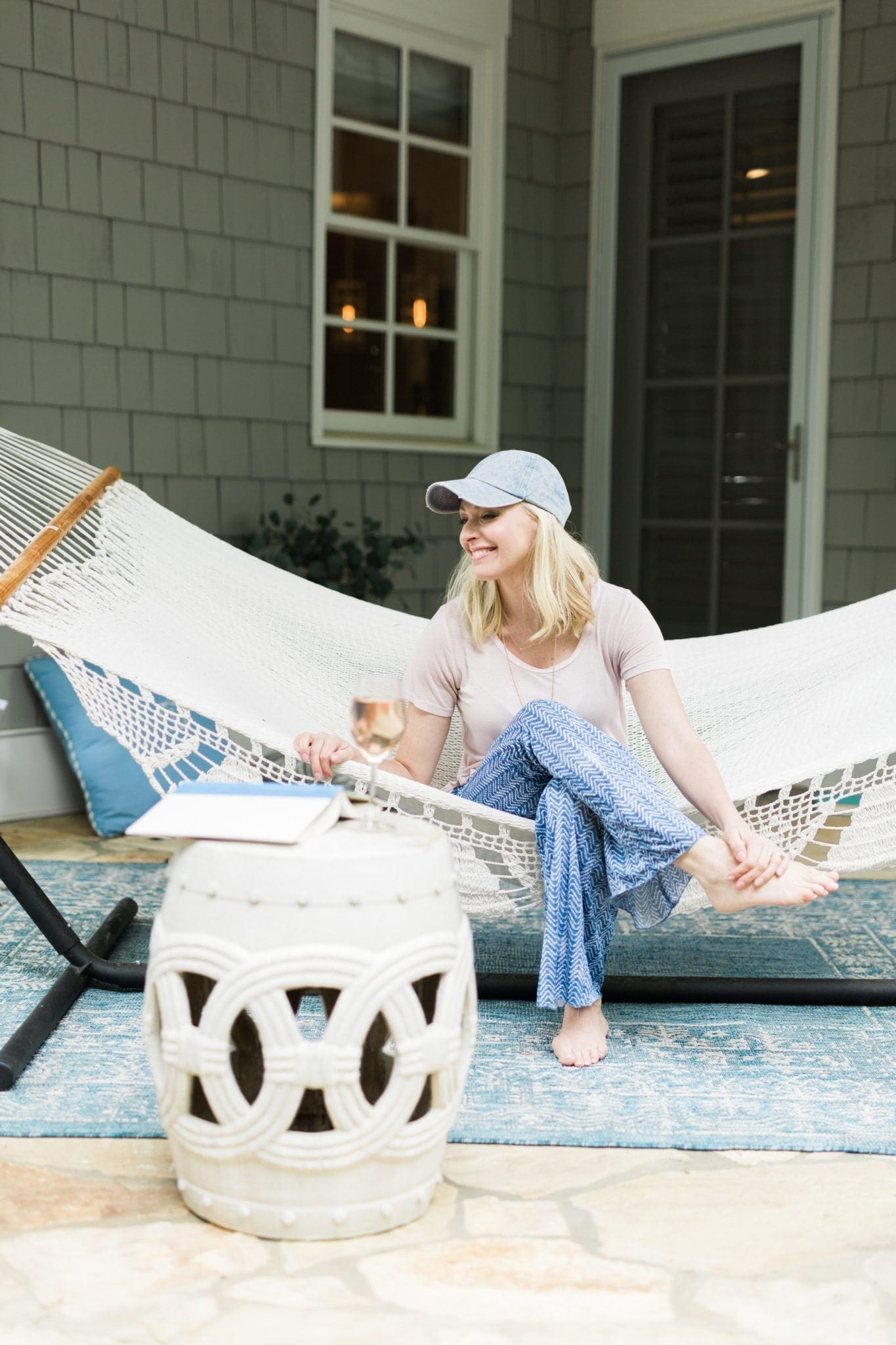 Home blogger Kelly Page in outdoor pretty hammock with garden stool.