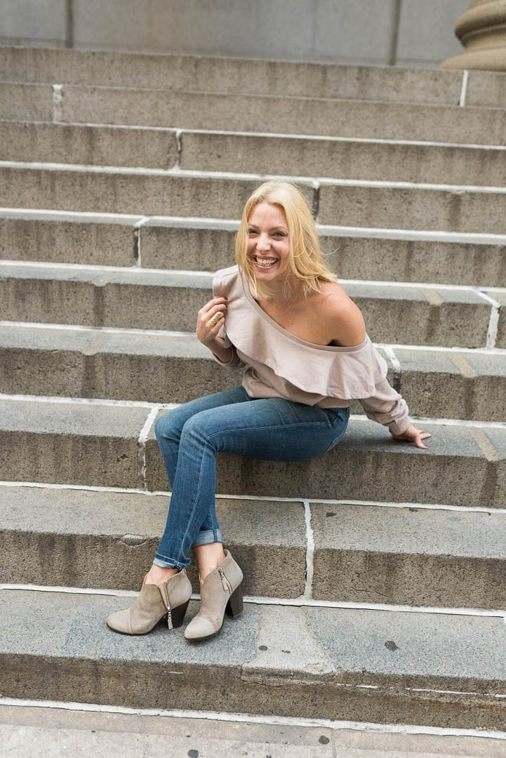 slouchy off the shoulder sweatshirt and booties with jeans on sidewalk in NYC.