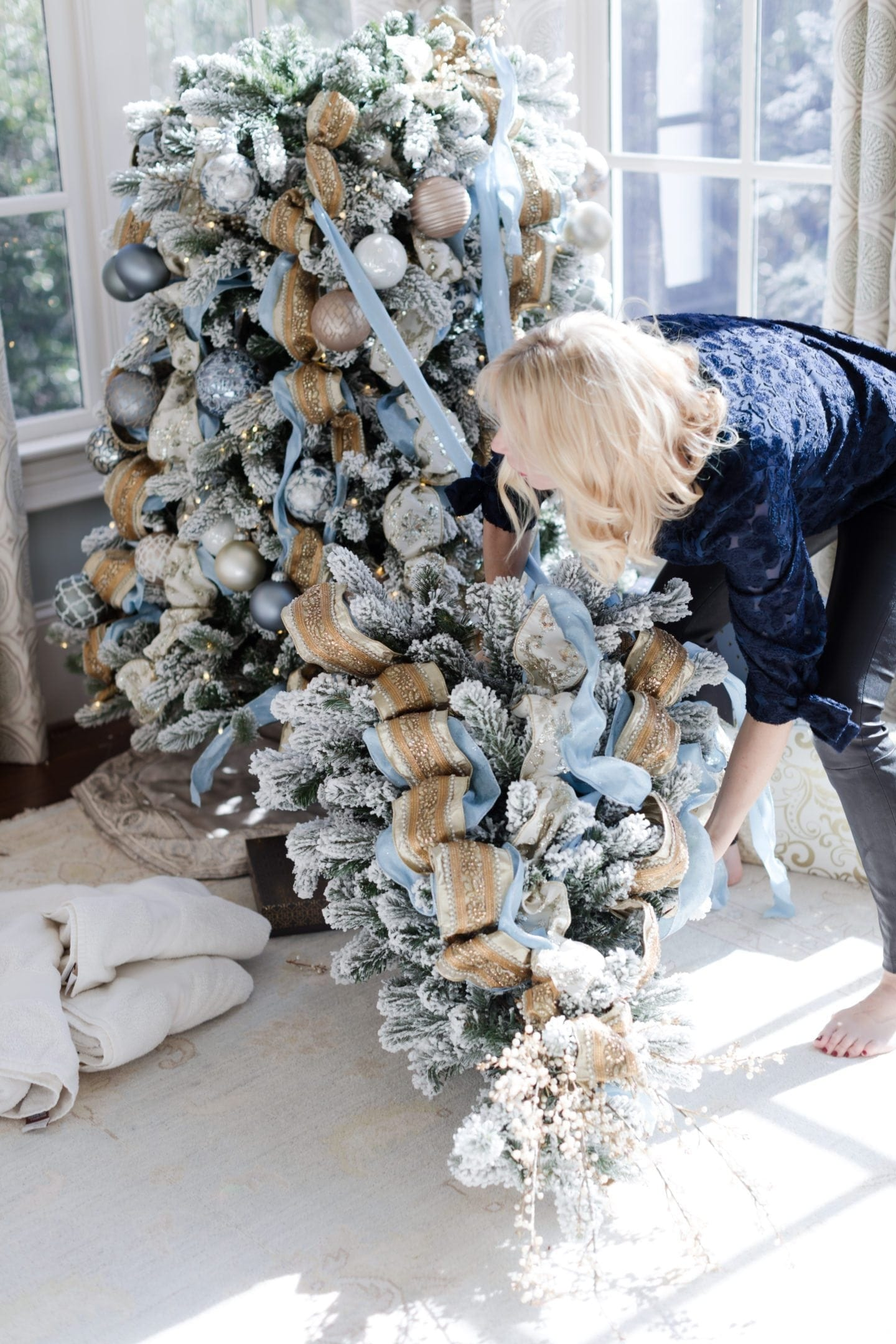 Learn how to set up an artificial tree. Gold intricate ribbon with blue sparkly ribbon.
