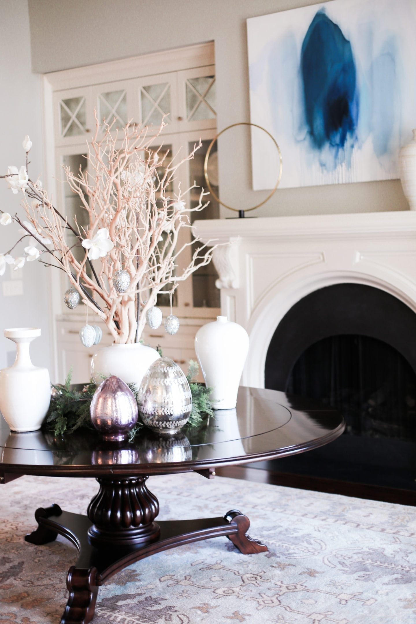 Easter centerpiece on a round dining room table. White urns with manzanita branches and faux magnolia leaves.