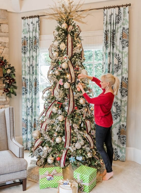 Decorating a tree with personalized ornaments from Kodak Moment Gifts.