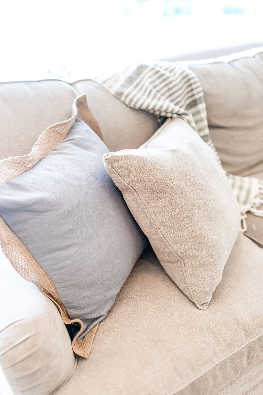 Burlap Throw Pillows in light blue and taupe on taupe gray chenille couch.