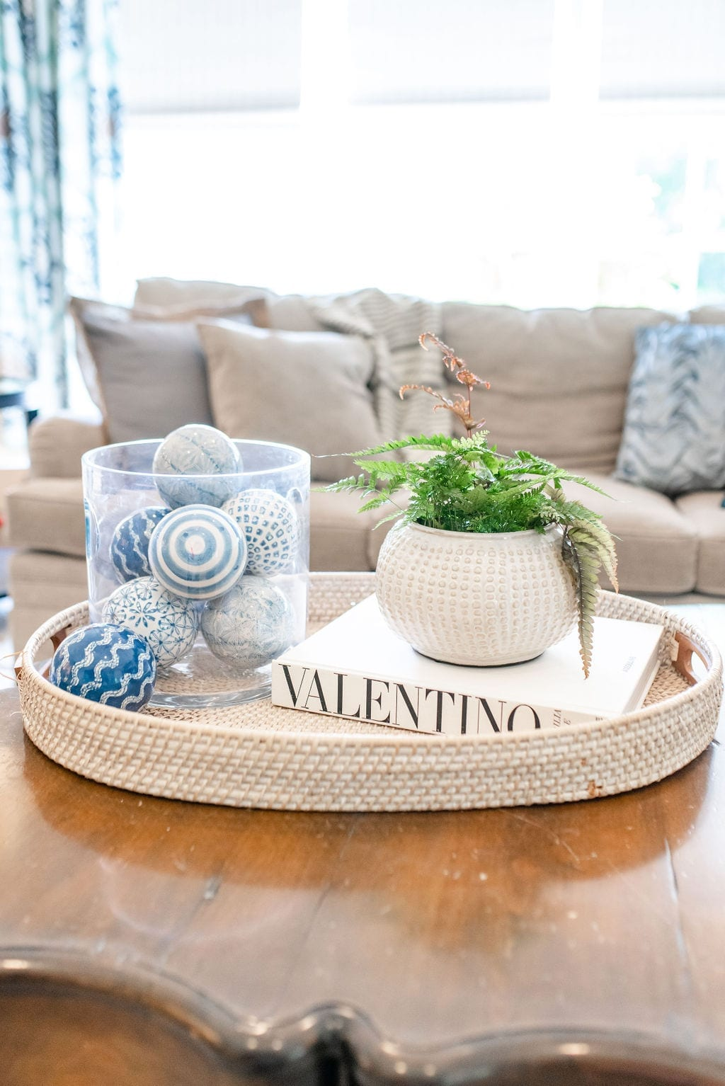 How to decorate your coffee table in neutral and blue colors. Coffee Table Decor Ideas with blue glass balls and blue drapes.