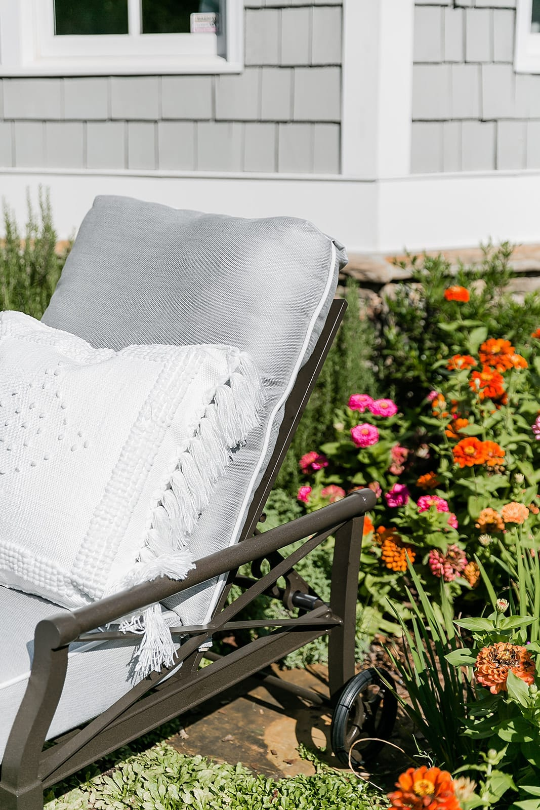 Quality outdoor furniture. Serena and Lily outdoor throw pillows with fringe and embroidery. Zinnia garden with cedar shake house in Atlanta, Georgia.