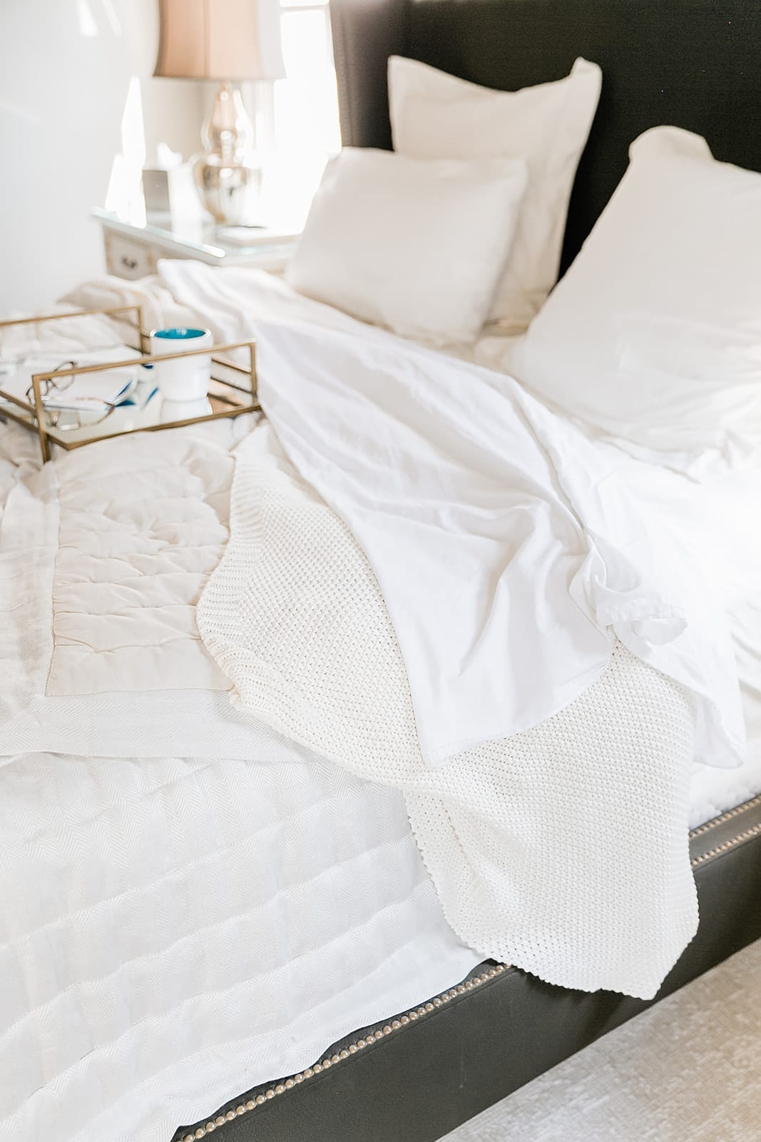 Ivory Hotel Sheets for fall. Dark bedroom with light ivory sheets and ivory knit blanket.