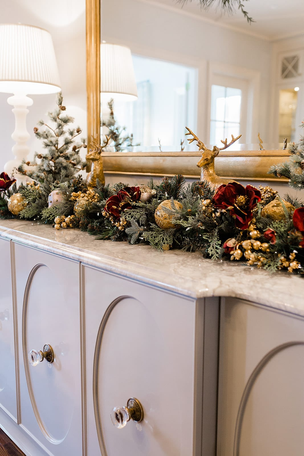 Gold reindeer decor for Christmas dining room buffet. Christmas tabletop idea with glamorous burgundy and gold holiday decor.