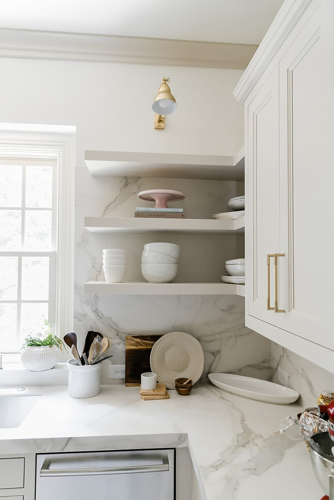 Floating Shelves in kitchen painted in Accessible beige with gold light and porcelain countertops.