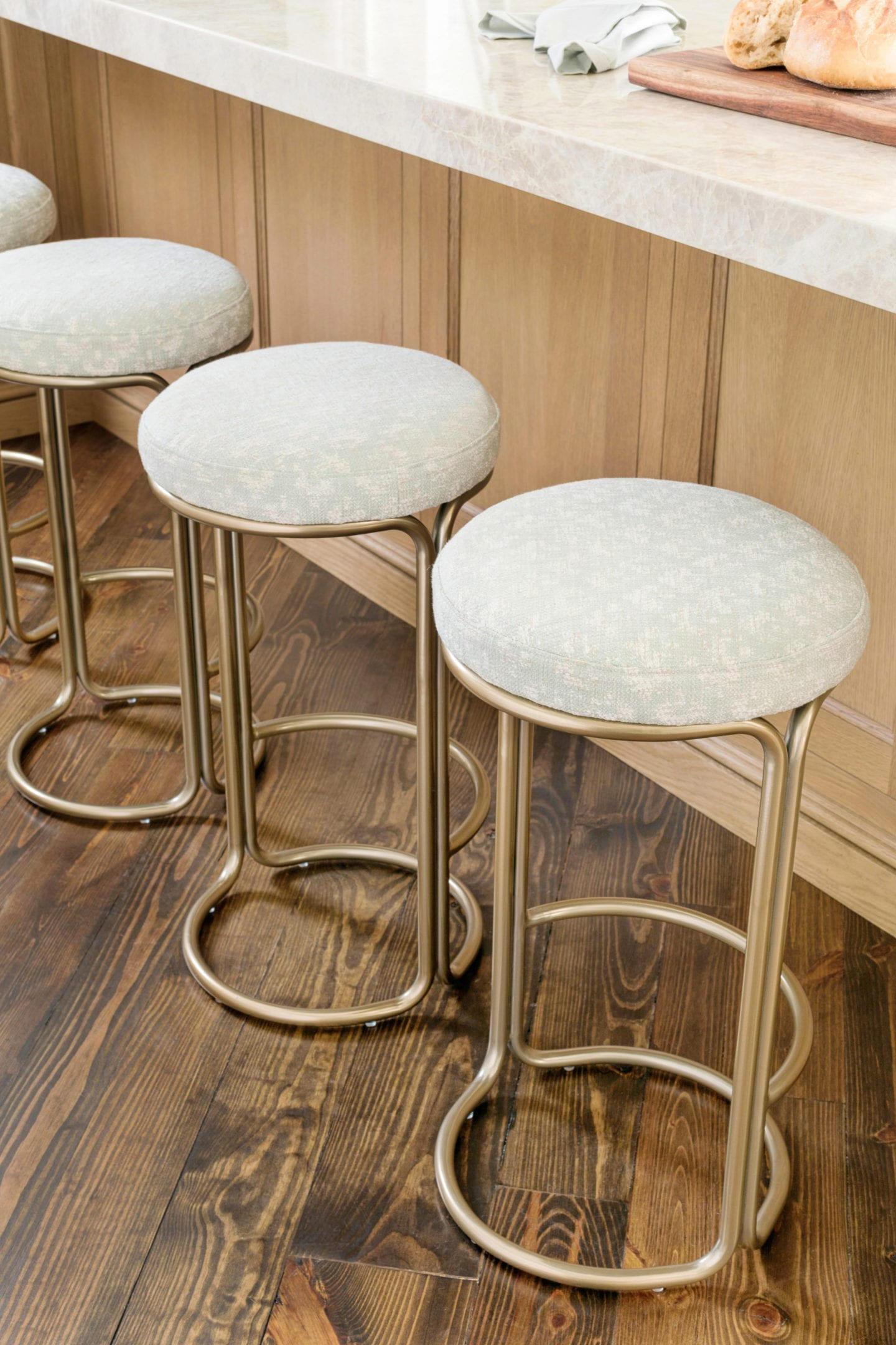 West Elm Counter Stools covered in Roma fabric with Taj Majal counter tops and stained wood kitchen floors.
