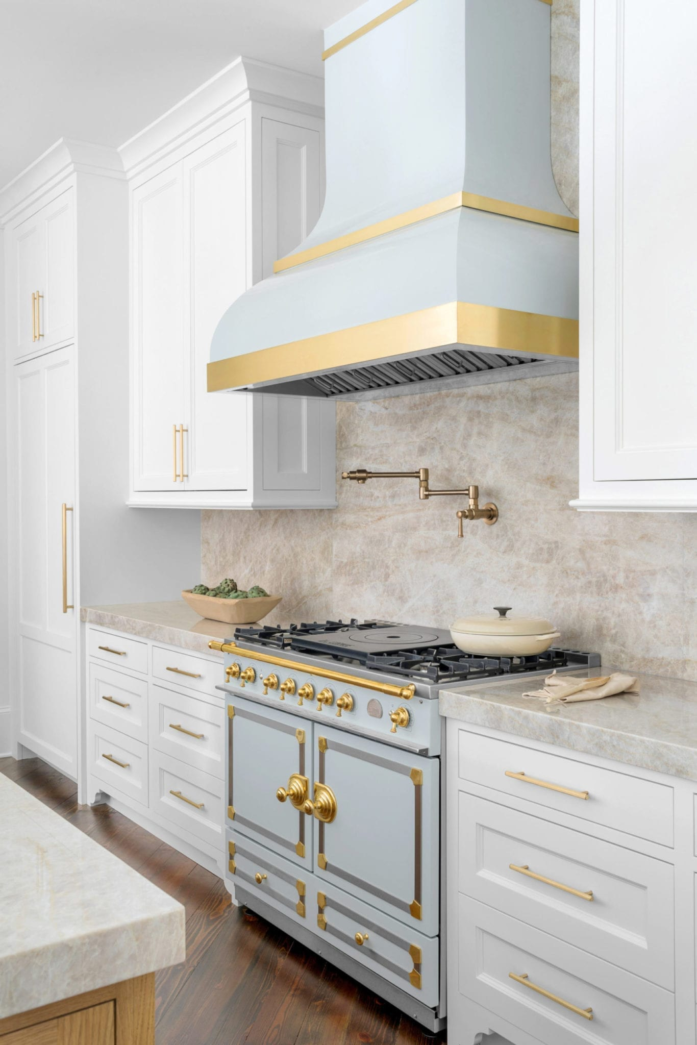 Blue LaCornue or LaCornue for Atlanta blogger Kelly Page, BlueGrayGals, kitchen. A Taj Majal countertop and full place keep the color simple but warm. A custom blue range hood was made with brass to work with the kitchen. White cabinets painted in Benjamin Moore White Dove create the pop of blue and white kitchen decor.