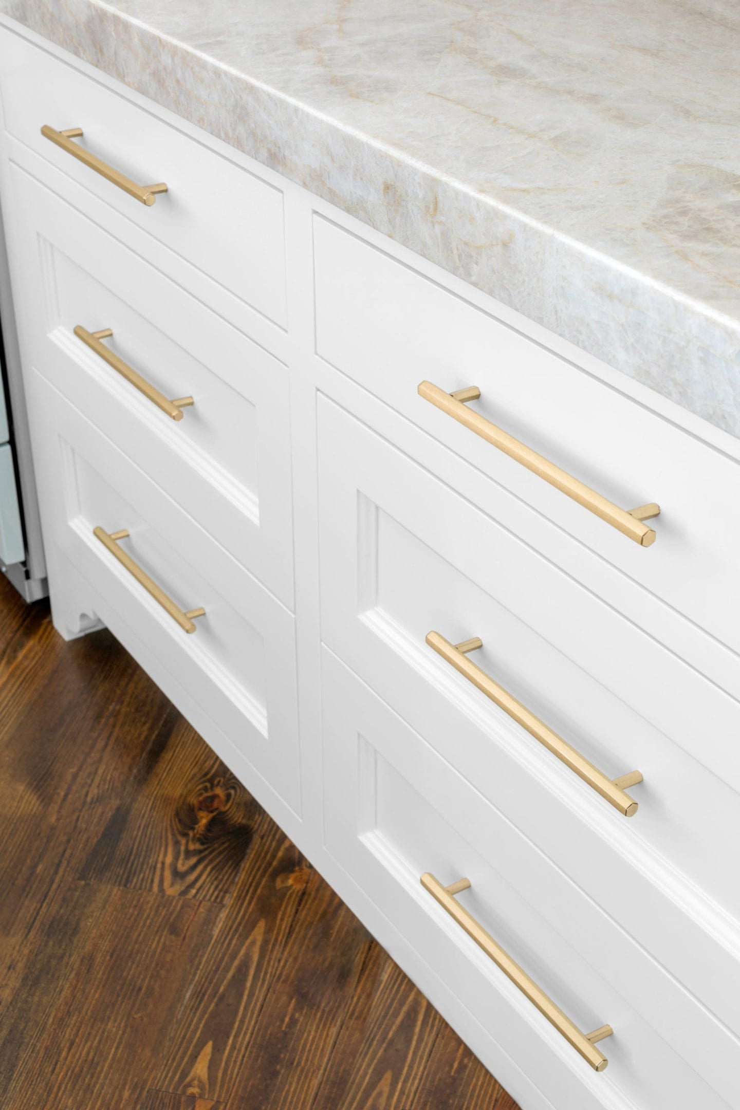 Gold Cabinet Hardware from Vesta on white cabinets with Taj Majal Quartzite countertops.