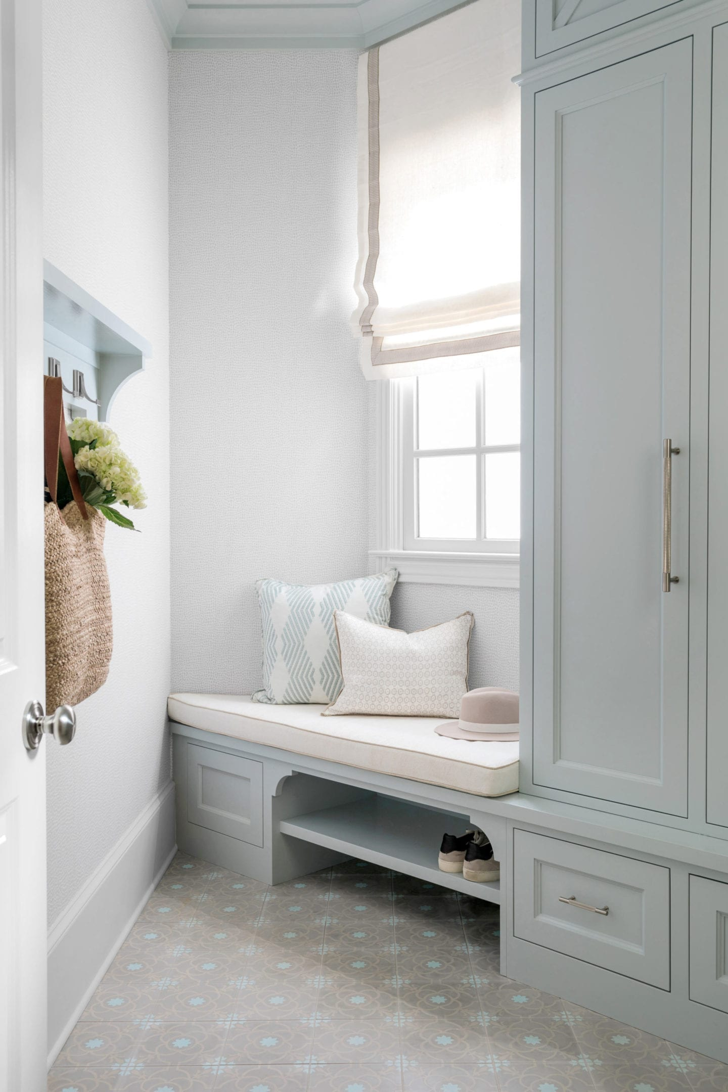 Mudroom Built In Cabinet Ideas with built in shoe storage, mudroom bench, blue cabinets and window covered in roman shade.