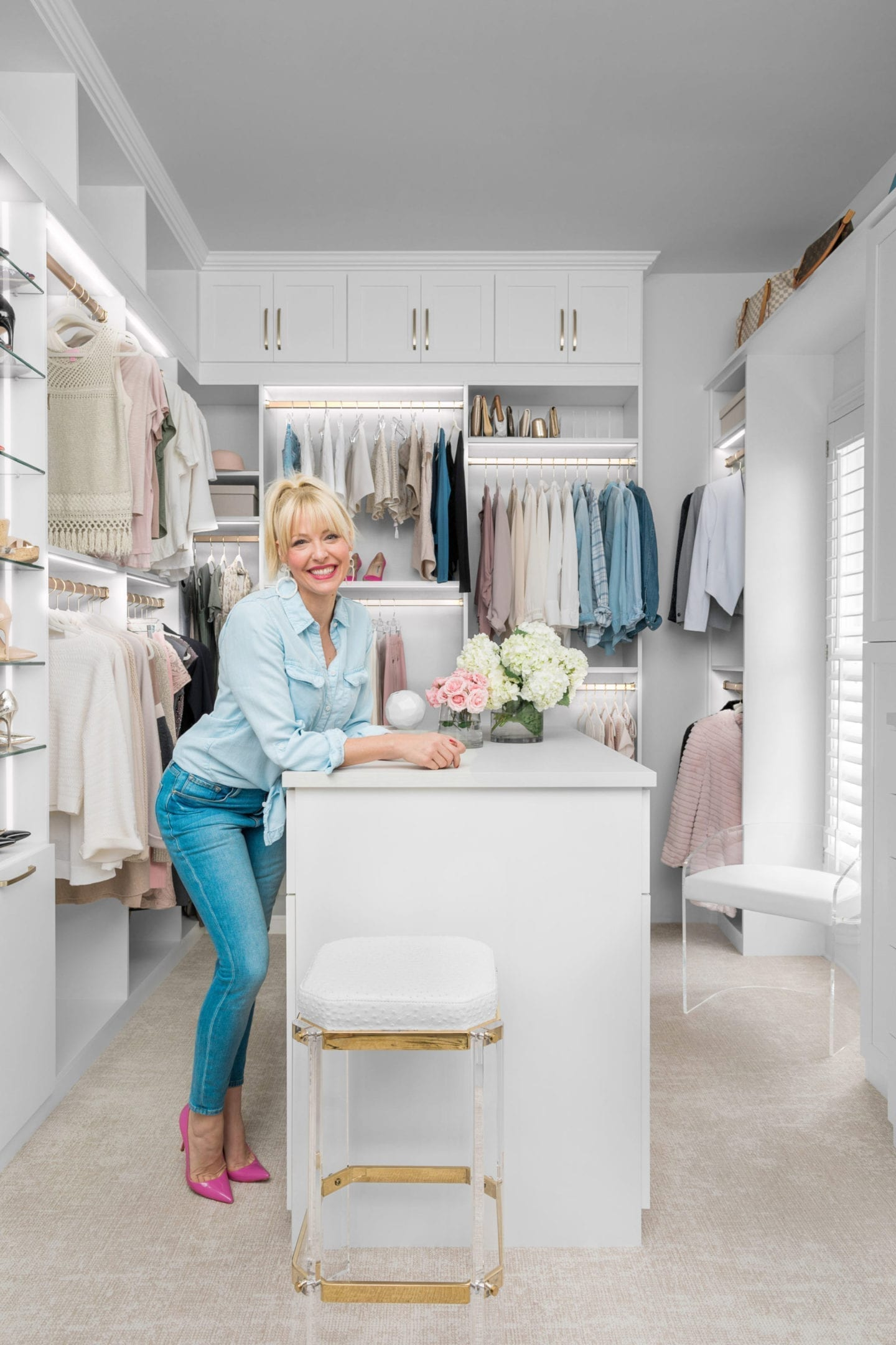 Kelly Page the home blogger behind BlueGrayGal stands in her newly remodel luxury closet with LED lighting created by California Closets.