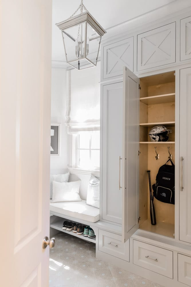 Mudroom organizing ideas. See our mudroom locker cubbies with doors, mudroom bench seat, roman shade and throw pillows all decorated with blue cabinetry, silver lantern pendant and patterned clement tile floor.