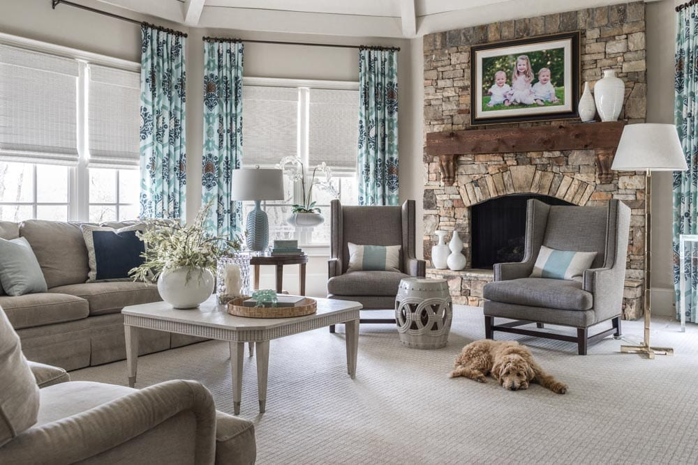 Traditional family room with stacked stone fireplace is framed with a tweed sitting area, ivory coffee table and a neutral soft layered with custom designer throw pillows.