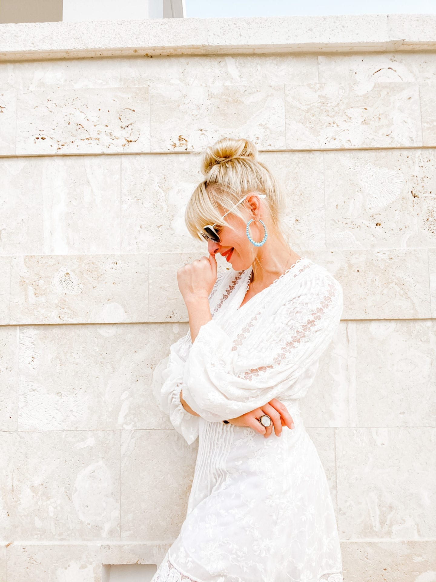 A new travel blog post from lifestyle blogger Kelly Page for blueGrayGal talking about Travel Trends 2020. Kelly poses in an Alexis white lace dresses with top knot bun.