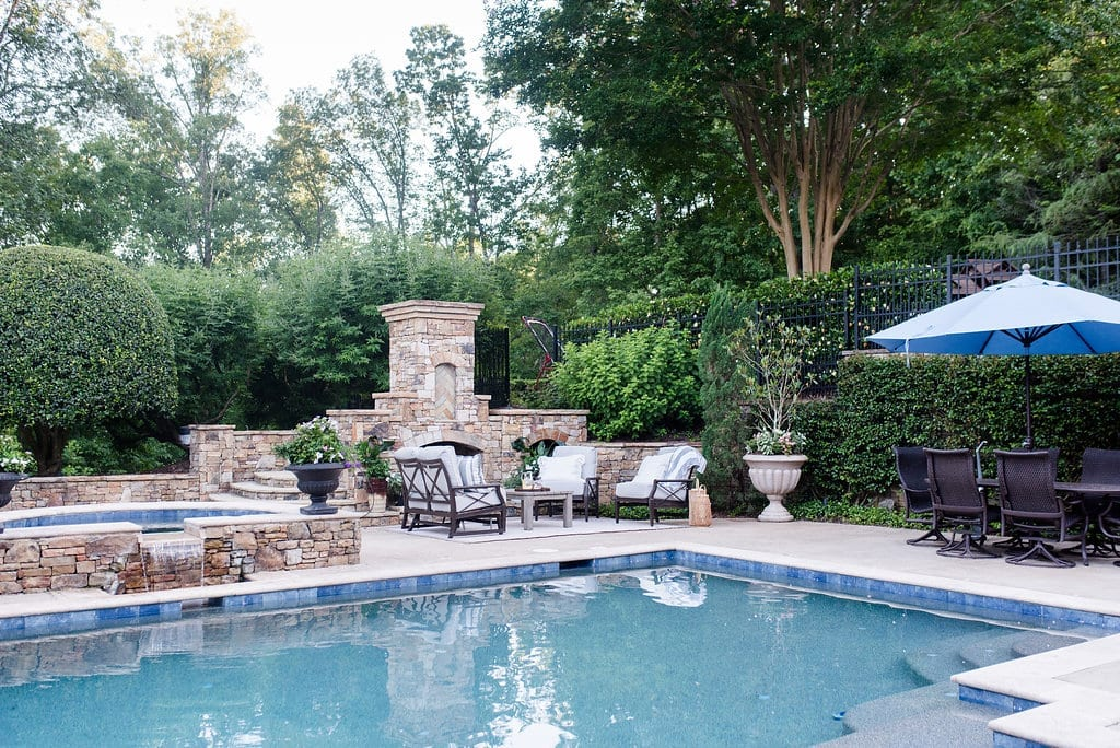 Blue Pool Tile is lined around a rectangular pool with hot tub and shallow shelf area. Pool landscaping is framed with lush greens.