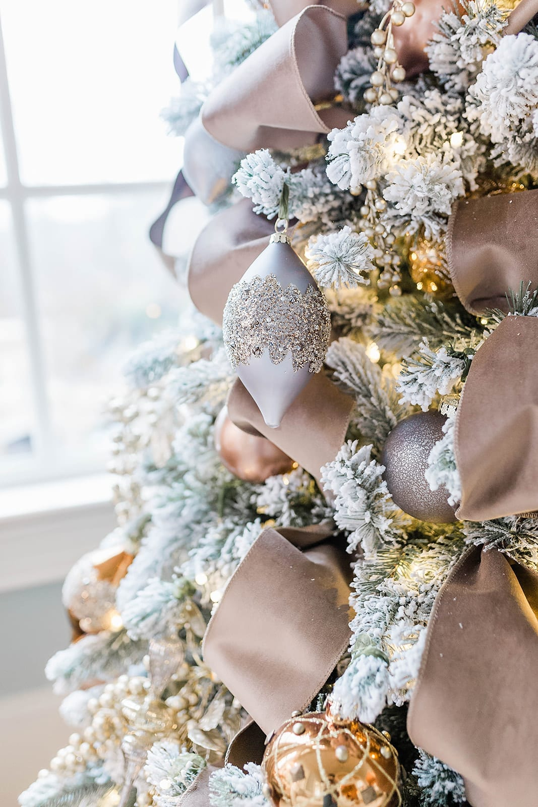 A Taupe velvet ribbon Christmas tree with blue ornaments from Frontgate collection and Frontgate tree topper. A gold Christmas skirt finishes off the taupe and navy blue accented flocked Christmas tree.