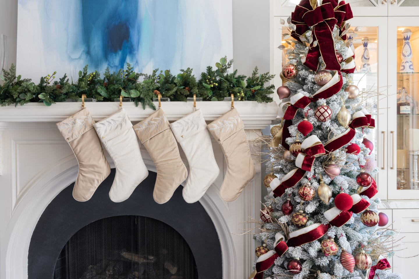 Burgundy and white Christmas Tree with silk satin stockings hung on white fireplace mantel.
